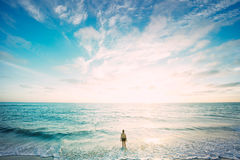 Woman Standing Facing Ocean Under White and Blue Sky Royalty Free Stock Photo