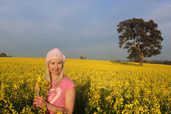 Woman standing in a field of golden canola farm Royalty Free Stock Images