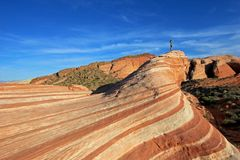 Woman standing on the the Fire Wave rock at sunset, Valley of Fire State Park, USA stock images