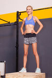 Woman standing on a fitness box Stock Images