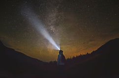 Woman is standing in the forest and pointing the Milky Way Stock Images
