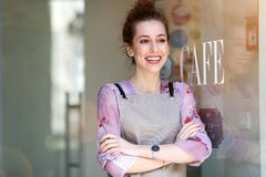 Woman standing in front of coffee shop stock photography