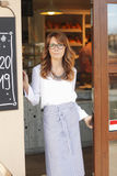 Woman standing in front of coffee shop Royalty Free Stock Images