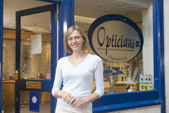 Woman standing at front entrance of opticians Royalty Free Stock Image