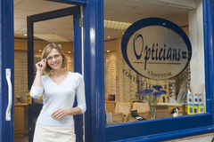 Woman standing at front entrance of optometrists Stock Images