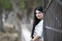 Woman standing front of metal garden fencing Royalty Free Stock Photo