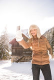 Woman standing in front of mountain house and taking selfie Royalty Free Stock Images