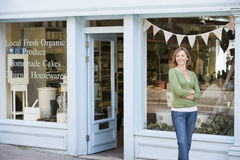 Woman standing in front of organic food store Royalty Free Stock Photos