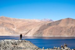 A woman standing in front of Pangong lake with mountains view and blue sky. Background Stock Image