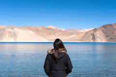 A woman standing in front of Pangong lake with mountains view and blue sky. Background Royalty Free Stock Photography
