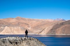 A woman standing in front of Pangong lake with mountains view and blue sky. Background Royalty Free Stock Image