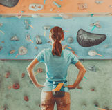 Woman standing in front of a practical climbing wall. Young woman standing in front of a practical climbing wall indoor and preparing to climb royalty free stock photos