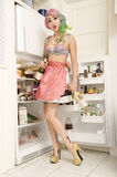 Woman standing in front of refrigerator with wine bottle Stock Photos