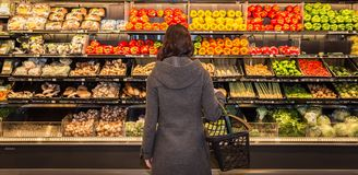 Woman standing in front of a row of produce in a grocery store. stock image