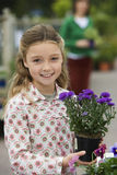 Woman standing in garden centre, focus on girl (7-9) holding purple pot plant in foreground, smiling Royalty Free Stock Images