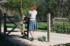 Woman standing by gate in forest Stock Photo