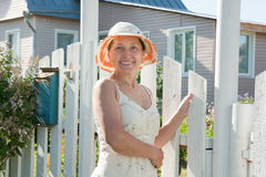 Woman standing at the gate of  house Stock Photos