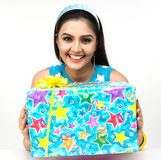 Woman standing with a gift box. Smiling woman standing with a gift box Stock Photography