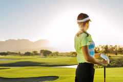 Woman standing on golf course on a sunny day. Rear view of young woman standing on golf course on a sunny day. Professional female golfer holding golf club on Stock Photos