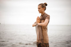 Woman standing a grateful namaste yoga pose on the beach next to the ocean in cloudy weather. Zen, meditation, peace. Stock Photo