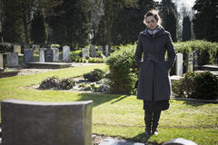 Woman standing at grave. Woman on graveyard looking at grave of deceased relative. Sad, mourning Stock Photos