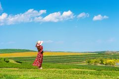 Woman standing on green grass in green tea field Stock Photo