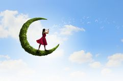 Woman standing on green moon Royalty Free Stock Images