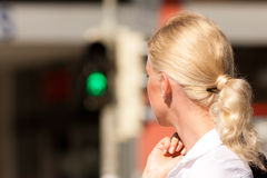 Woman standing at green traffic light Royalty Free Stock Photo