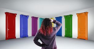 Doors choice. Woman standing in hallway in front of multicolored doors. Concept of hard choice and opportunities Royalty Free Stock Photos