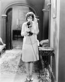 Woman standing in the hallway talking on a candlestick telephone Stock Images