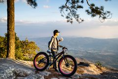 A woman standing with hand holding a bottle of water beside a bicycle on rocky mountain. Looking out at scenic natural view and beautiful blue sky stock image