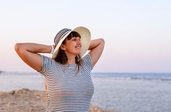 Woman Standing with Hands Behind Head on Beach royalty free stock photos