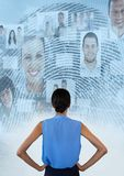 Woman standing hands on hips looking at interface of faces and a fingerprint. Digital composite of Woman standing hands on hips looking at interface of faces and Royalty Free Stock Images