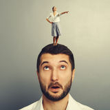 Woman standing on the head of amazed man. Small young women pointing at something and standing on the head of amazed man Stock Images