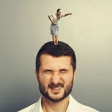 Woman standing on the head of dissatisfied man Royalty Free Stock Photography