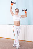 Woman standing held up dumbbells Stock Photography