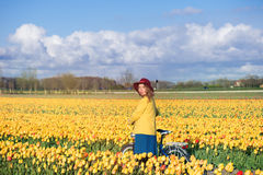 Woman standing with her bike in tulips fields Stock Photography