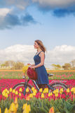 Woman standing with her bike in tulips fields Stock Photos