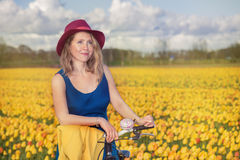 Woman standing with her bike in tulips fields Stock Photo
