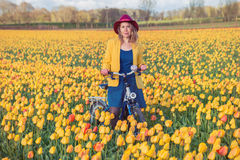 Woman standing with her bike in tulips fields Royalty Free Stock Photos