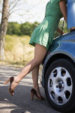 Woman standing by her broken car. Woman standing by broken car and looking to engine Royalty Free Stock Photo