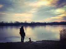 Woman standing with her dog at the lakeside of a frozen lake in winter stock image
