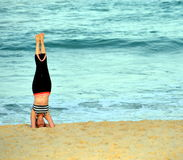Woman standing on her head and doing yoga on the beach Royalty Free Stock Image