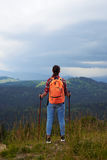 Woman standing with hiking poles on top of mountain Stock Image