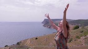 Woman standing on the hill near sea, windy day. Hands up stock video