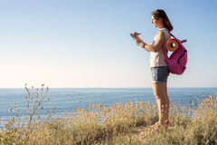 Woman standing on the hill and writes in notebook Stock Image