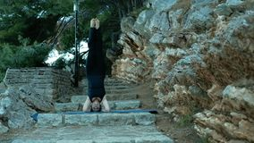 Woman standing on his head on stone steps on sports mat. stock footage