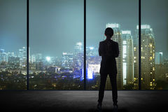 Woman standing in his office looking at the city at night Stock Photos