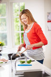Woman Standing At Hob Preparing Meal In Kitchen Stock Photography