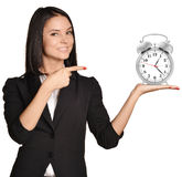 Woman standing and holding alarm clock on pointing Royalty Free Stock Photography